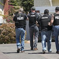 Heavily armed San Diego police officers approach a house thought to be the home of 19-year-old John T. Earnest, the alleged shooter in the fatal attack at a synagogue in Poway on April 27, 2019, in San Diego, California. (John Gibbins/ The San Diego Union-Tribune via AP)