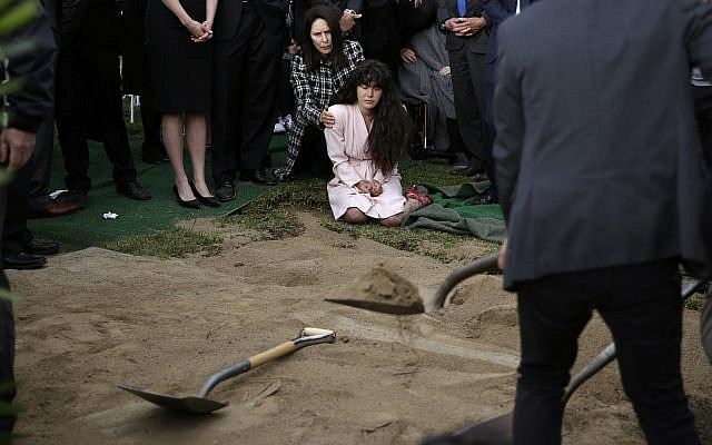 Hannah Kaye, (C) the daughter of Poway Chabad shooting victim Lori Gilbert-Kaye, sits on the ground with her aunt, Randi Grossman, as the last shovels of dirt cover her mother's grave during funeral services, on April 29, 2019, in San Diego. (AP Photo/Gregory Bull)
