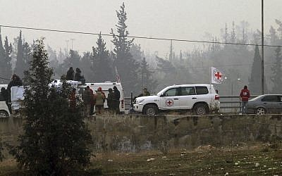 In this photo released by the Syrian official news agency SANA, civilians gather near the Red Cross vehicles for evacuation from eastern Aleppo, Syria, Friday, Dec. 16, 2016. (SANA via AP)