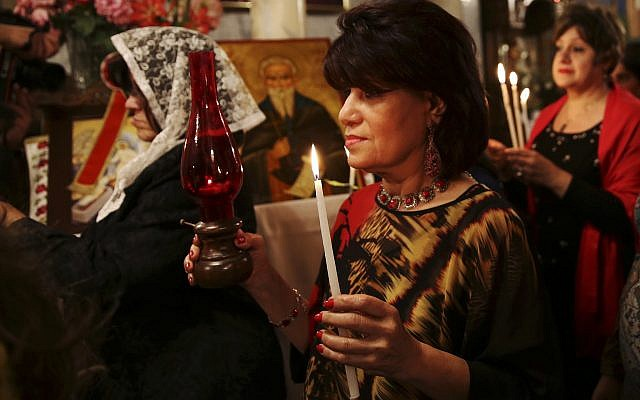Orthodox Christian worshippers hold candles during the Easter Eve service at the St. Porphyrios church in Gaza City, Saturday, April 15, 2017. (AP Photo/Adel Hana)
