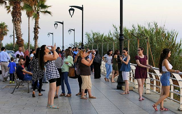 Tourists takes pictures, as the sun sets over the Mediterranean Sea in Beirut, Lebanon, on June 30, 2017. (AP Photo/Hassan Ammar/File)