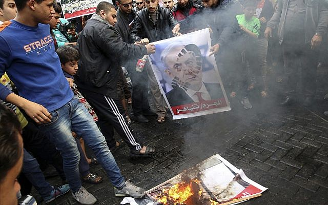 Illustrative: Hamas supporters burn a picture of the Prime Minister Benjamin Netanyahu during protest against US President Donald Trump's decision to recognize Jerusalem as Israel's capital, in Jebaliya Refugee Camp, Gaza Strip, December 8, 2017. (AP Photo/Adel Hana)