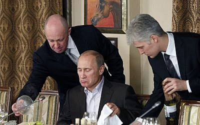 In this Nov. 11, 2011 photo, businessman Yevgeny Prigozhin, left, serves food to Russian Prime Minister Vladimir Putin, center, during dinner at Prigozhin's restaurant outside Moscow, Russia (AP Photo/Misha Japaridze, Pool, File)