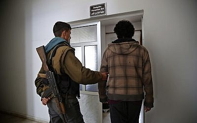 Illustrative: In this photo from April 3, 2018, a Kurdish prison security guard, left, escorts a 19-year-old former fighter of the Islamic State extremist group, into the courtroom of a Kurdish-run terrorism court, in Qamishli, north Syria. (AP Photo/Hussein Malla)