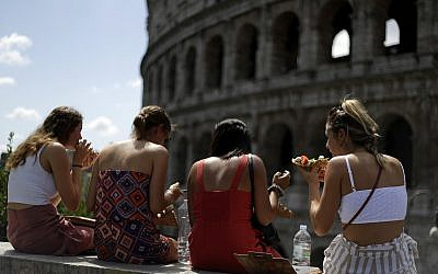 Illustrative: Tourists enjoy slices of pizza as they sit in front of Rome's Colosseum, July 17, 2018. (AP Photo/Gregorio Borgia)