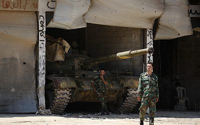 File: Syrian soldiers stand guard at their military post on the entrance of the central Syrian town of Rastan, Homs province, Syria, Tuesday, July 17, 2018. (AP Photo/Hassan Ammar)