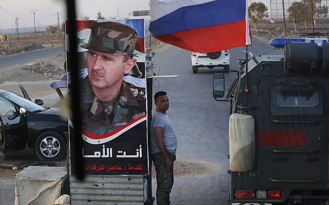 Syrian army soldier stands at a check-point as Russian military police vehicle, right, passes by near the village of Almajdiyeh, Syria, Tuesday, Aug. 14, 2018. (AP/Sergei Grits)