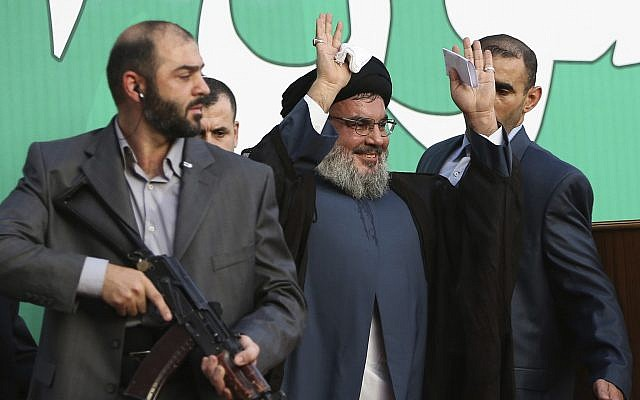 In this photo from September 17, 2012, Hezbollah leader Hassan Nasrallah, center, escorted by his bodyguards, waves to a crowd of tens of thousands of supporters during a rally in Beirut, Lebanon. (AP Photo/Hussein Malla, File)