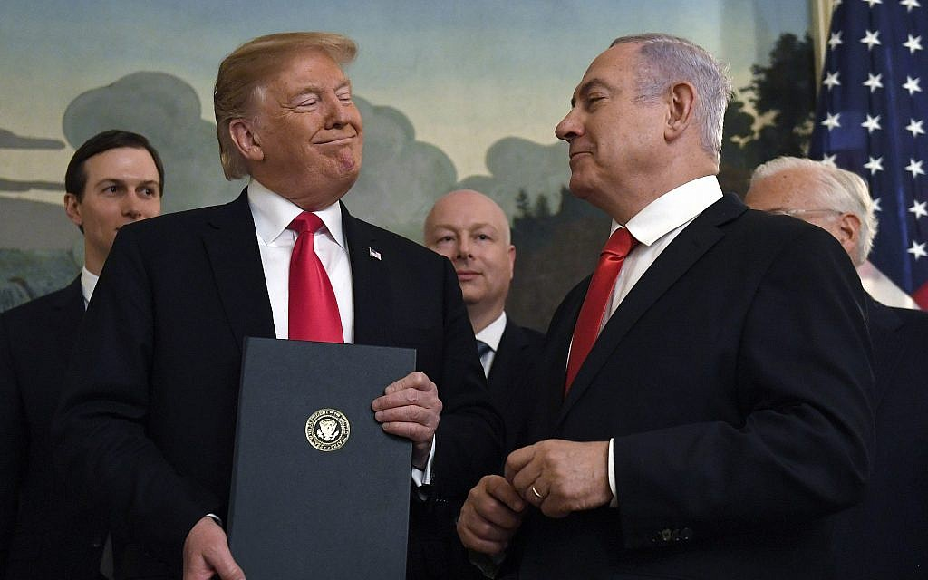 US President Donald Trump smiles at Israeli Prime Minister Benjamin Netanyahu, right, after signing a proclamation formally recognizing Israel's sovereignty over the Golan Heights, in the Diplomatic Reception Room at the White House in Washington, March 25, 2019 (AP Photo/Susan Walsh)