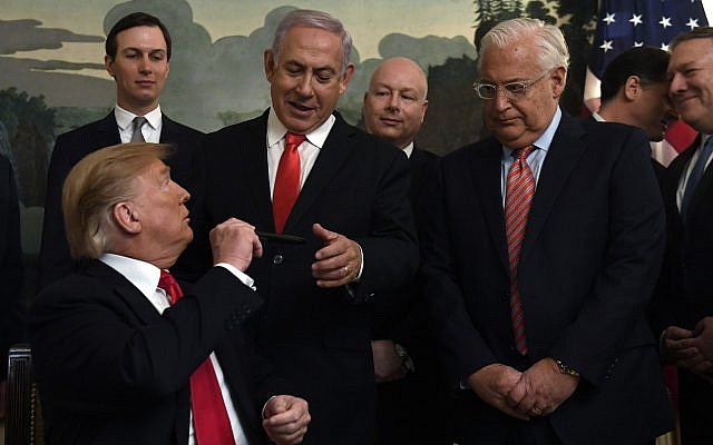 US President Donald Trump, left, turns to give a pen to Israeli Prime Minister Benjamin Netanyahu, center, at the White House in Washington, March 25, 2019 after signing the official proclamation formally recognizing Israel's sovereignty over the Golan Heights. From left, White House adviser Jared Kushner, US special envoy Jason Greenblatt, US Ambassador to Israel David Friedman, Israeli Ambassador to the US Ron Dermer, and Secretary of State Mike Pompeo. (AP/Susan Walsh)