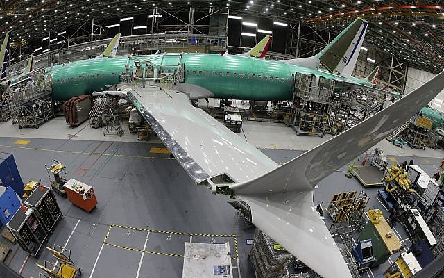In this photo taken with a fish-eye lens, a Boeing 737 MAX 8 airplane sits on the assembly line during a brief media tour in Boeing's 737 assembly facility, Wednesday, March 27, 2019, in Renton, Washington (AP Photo/Ted S. Warren)