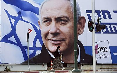 A woman walks by an election campaign billboard in Tel Aviv, March 28, 2019, showing Prime Minister Benjamin Netanyahu. (AP/Oded Balilty)