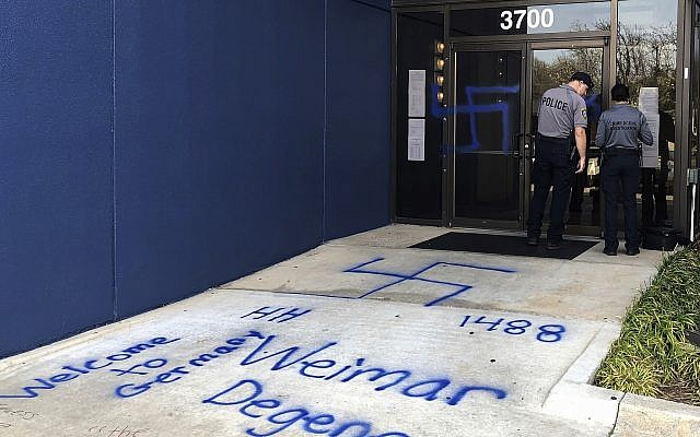 Law enforcement officers investigate racist and anti-Semitic graffiti in front of a building that houses the Oklahoma Democratic Party headquarters Thursday, March 28, 2019, in Oklahoma City. Former Democratic Gov. David Walters said Thursday that vandals spray-painted derogatory remarks about various racial and ethnic groups outside the building. Swastikas were also spray-painted onto the doors. Walters and his wife, Rhonda, own the building, which also houses other tenants. (AP Photo/Adam Kealoha Causey)
