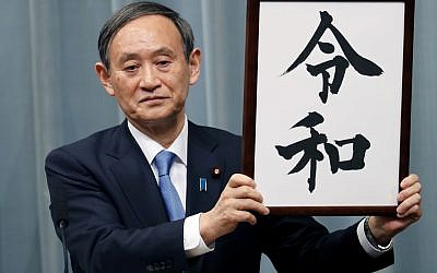 "Japan's Chief Cabinet Secretary Yoshihide Suga unveils the name of new era ""Reiwa"" at the prime minister's office in Tokyo, April 1, 2019 (AP Photo/Eugene Hoshiko)"