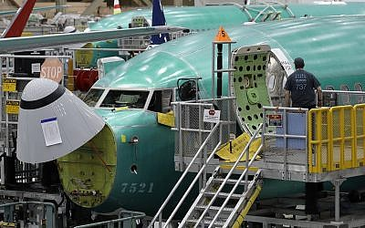In this March 27, 2019, file photo, a worker enters a Boeing 737 MAX 8 airplane during a brief media tour of Boeing's 737 assembly facility in Renton, Washington (AP Photo/Ted S. Warren, File)