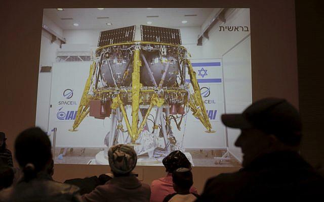 People watch the live broadcast in Netanya, on April 11, 2019, of the SpaceIL Beresheet lunar landing attempt. (AP/Ariel Schalit)