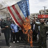 Protesters burn a representation of the American flag during a rally against the US's decision to designate Iran's powerful Revolutionary Guards as a foreign terrorist organization, after their Friday prayers at the Enqelab-e-Eslami (Islamic Revolution) square in Tehran, Iran on April 12, 2019. (AP/Vahid Salemi)