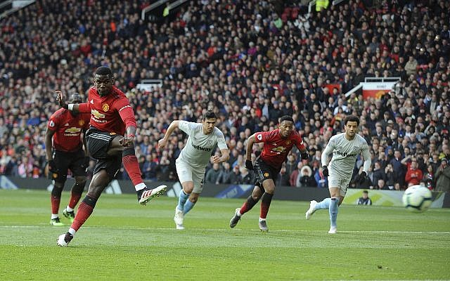 Manchester United's Paul Pogba scores the opening goal from the penalty spot during the English Premier League soccer match between Manchester United and West Ham United at Old Trafford stadium in Manchester, England, Saturday, April 13, 2019. (AP/Rui Vieira)