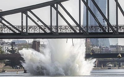 A large water fountain rises behind the Iron Bridge when a 250 kilogram American bomb from World War II in the Main River is detonated with a blast in Frankfurt, Germany, April 14, 2019. (Frank Rumpenhorst/dpa via AP)