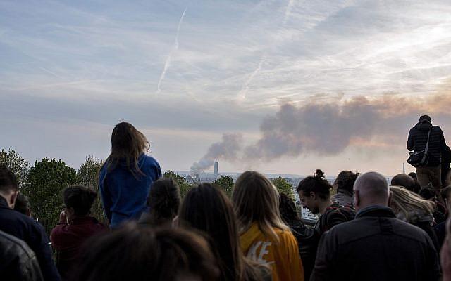 People watch Notre Dame cathedral burning in Paris, Monday, April 15, 2019. (AP/Rafael Yaghobzadeh)