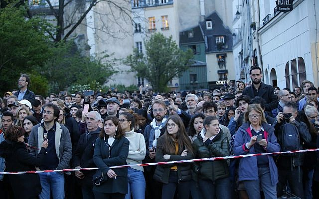 People watch as flames and smoke rise from Notre Dame cathedral as it burns in Paris, Monday, April 15, 2019. (AP/Michel Euler)
