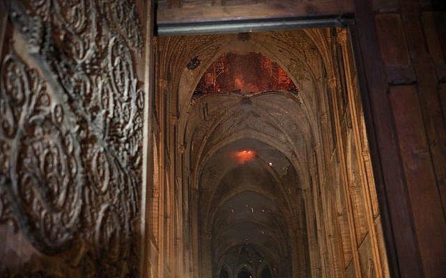 Smoke and flames are seen in the interior of Notre Dame cathedral in Paris, Monday, April 15, 2019.  (Philippe Wojazer/Pool via AP)