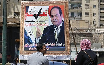 People walk past a banner supporting proposed amendments to the Egyptian constitution with a poster of Egyptian President Abdel-Fattah el-Sissi in Cairo, Egypt, April 16, 2019. (AP/Amr Nabil)