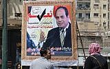 People walk past a banner supporting proposed amendments to the Egyptian constitution with a poster of Egyptian President Abdel-Fattah el-Sissi in Cairo, Egypt, Tuesday, April 16, 2019 (AP Photo/Amr Nabil)