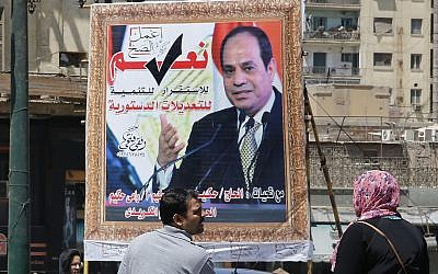 People walk past a banner supporting proposed amendments to the Egyptian constitution with a poster of Egyptian President Abdel-Fattah el-Sissi in Cairo, Egypt, on April 16, 2019. (AP/Amr Nabil)