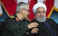 In this photo released by the official website of the office of the Iranian Presidency, President Hassan Rouhani, right, listens to Chief of the General Staff of the Armed Forces Gen. Mohammad Hossein Bagheri during the army parade commemorating National Army Day in front of the shrine of the late revolutionary founder Ayatollah Khomeini, just outside Tehran, Iran on April 18, 2019. (Iranian Presidency Office via AP)