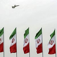 In this photo released by the official website of the office of the Iranian Presidency, a fighter jet flies over Iranian flags during the army parade commemorating National Army Day in front of the shrine of the late revolutionary founder Ayatollah Khomeini, just outside Tehran, Iran on April 18, 2019. (Iranian Presidency Office via AP)