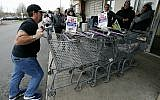 A temporary worker rolls shopping carts past striking workers outside a Stop & Shop supermarket in Boston, Thursday, April 18, 2019. (AP/Michael Dwyer)