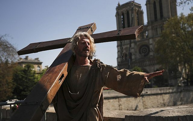 A man carries a wooden cross outside the Notre Dame Cathedral as part of a demonstration in Paris, April 20, 2019 (AP Photo/Francisco Seco)