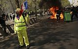 A protester waves a French flag as a dumpster burns in the background during a yellow vest demonstration in Paris, April 20, 2019. (AP Photo/Francisco Seco)