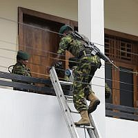 A Sri Lankan police commando enters a house suspected to be a hideout of militants following a shoot out in Colombo, Sri Lanka, on April 21, 2019. (AP/Eranga Jayawardena)
