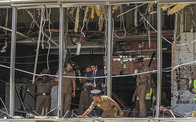 A Sri Lankan Police officer inspects a blast spot at the Shangri-la hotel in Colombo, Sri Lanka, April 21, 2019. (AP/Chamila Karunarathne)