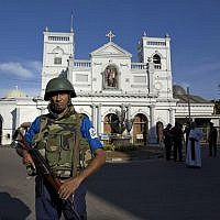 Sri Lankan air force officers and clergy stand outside St. Anthony's Shrine, a day after a blast in Colombo, Sri Lanka, April 22, 2019. (AP Photo/Gemunu Amarasinghe)
