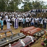 A priest conducts a mass burial for Easter Sunday bomb blast victims in Negombo, Sri Lanka on April 24, 2019. (AP Photo/Gemunu Amarasinghe)