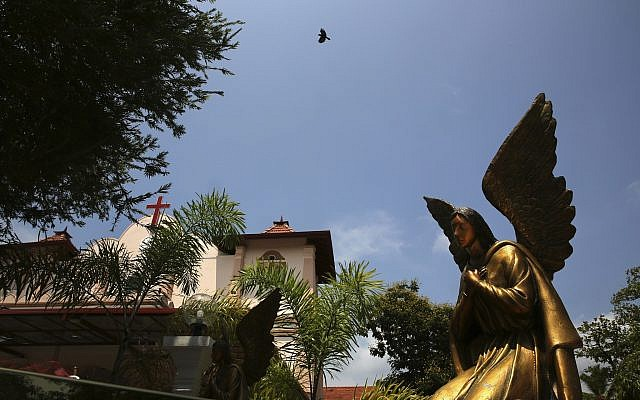 In this April 25, 2019 photo, a bird flies over St. Sebastian's Church, where a suicide bomber blew himself up on Easter Sunday in Negombo, north of Colombo, Sri Lanka (AP Photo/Manish Swarup)