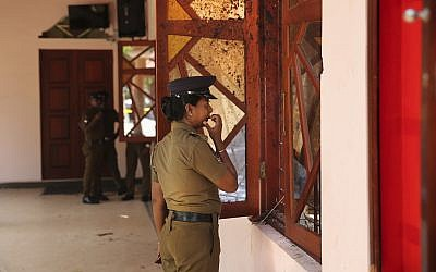 In this April 25, 2019 photo, a Sri Lankan policewoman looks at the damage inside St. Sebastian's Church, one of the sites of Easter Sunday's bombings, in Negombo, north of Colombo, Sri Lanka (AP Photo/Manish Swarup)