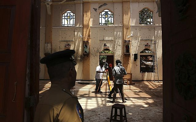 In this April 25, 2019 photo, a policeman stands guard, as surveyors work at St. Sebastian's Church, where a suicide bomber blew himself up on Easter Sunday in Negombo, north of Colombo, Sri Lanka (AP Photo/Manish Swarup)