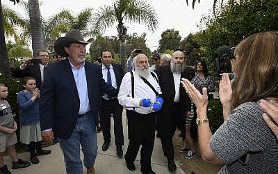 Poway mayor Steve Vaus  (L) accompanies Rabbi Yisroel Goldstein as he arrives at a news conference at the Chabad of Poway synagogue, Sunday, April 28, 2019, in Poway, Calif.  (AP Photo/Denis Poroy)