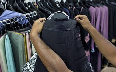A salesman covers the face of a mannequin with a niqab cafe veil at a women's clothing shop in Kattankudy, Sri Lanka, April 29, 2019. (AP/Gemunu Amarasinghe)