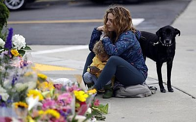 A woman and a child pause at a growing memorial across the street from the Chabad of Poway synagogue in Poway, California, following a deadly shooting there. April 29, 2019 (AP Photo/Greg Bull)