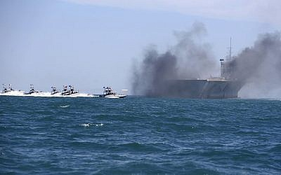 In this picture released by the semi-official Iranian Fars news agency on February 25, 2015, Revolutionary Guard speedboats assault a replica of a US aircraft carrier during large-scale naval drills near the entrance of the Persian Gulf, Iran. (AP/Fars News Agency, Hamed Jafarnejad)