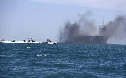 In this picture released by the semi-official Iranian Fars news agency on Wednesday, Feb. 25, 2015, Revolutionary Guard speedboats assault a replica of a US aircraft carrier during large-scale naval drills near the entrance of the Persian Gulf, Iran. (AP/Fars News Agency, Hamed Jafarnejad)