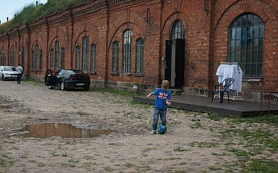 A boy playing soccer at the entrance to the former concentration camp known as the Seventh Fort in Kaunas, Lithuania, on July 12, 2016. (JTA/Cnaan Liphshiz)