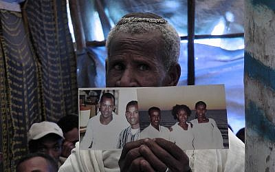 An Ethiopian worshiper at the synagogue in Addis Ababa praying and holding photos of family members living in Israel. (Bernard Dichek/ Times of Israel)