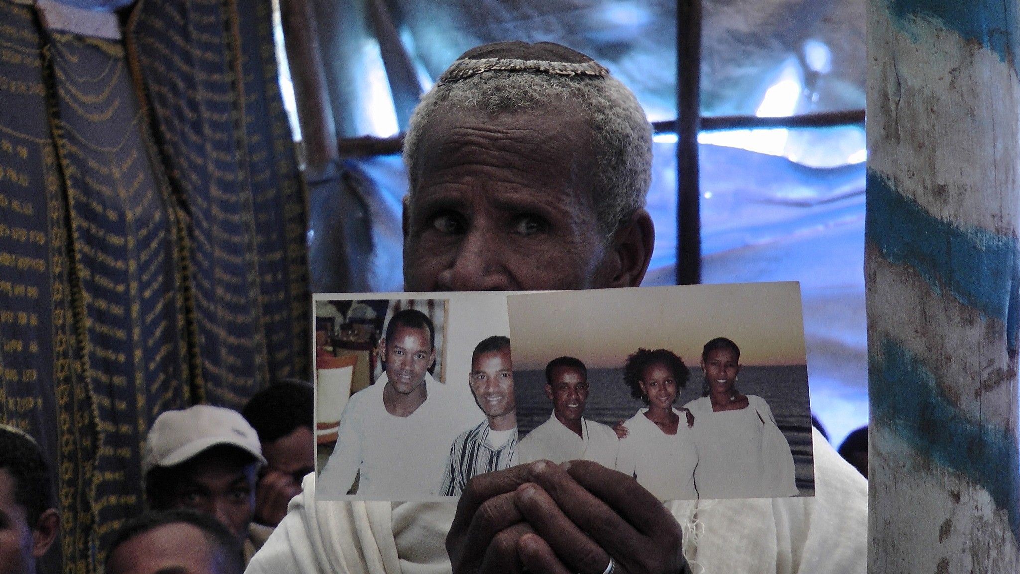 An Ethiopian worshiper at the synagogue in Addis Ababa praying and holding photos of family members living in Israel. (Bernard Dichek/Times of Israel)