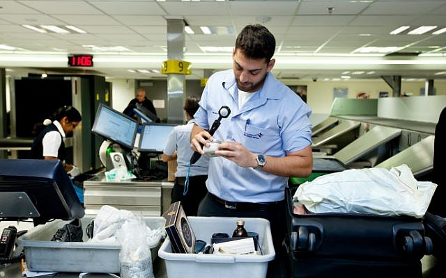 File: A worker at Ben Gurion Airport seen checking passenger luggage in 2014 (Moshe Shai/FLASH90)